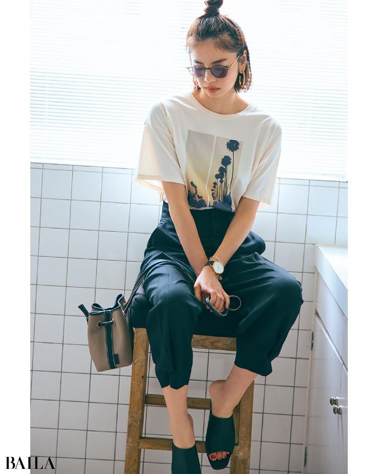 大人なムードのリゾート風景のフォトTシャツと黒パンツコーデの佐藤晴美