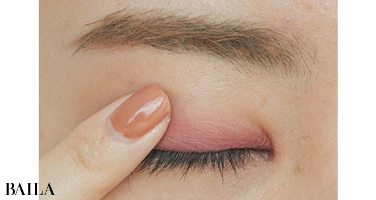 ピンクの境目を指でかるくなぞってぼかす。下まぶたは黒マスカラだけにとどめて抜け感を