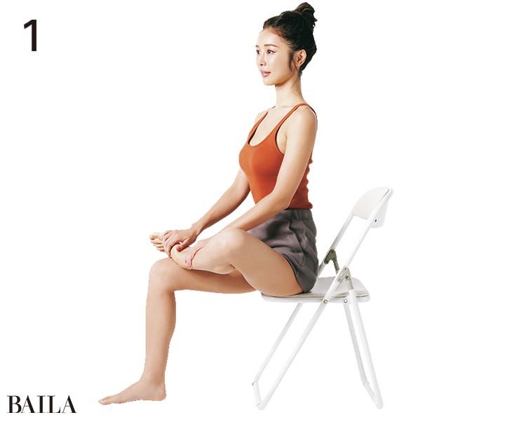 ミルフィーユポイント、仙骨、尾骨すべてをほぐせるストレッチ。椅子に座り、右ひざを曲げ、左足を右のももへ。右手を左足首、左手で左すねを下へと押す
