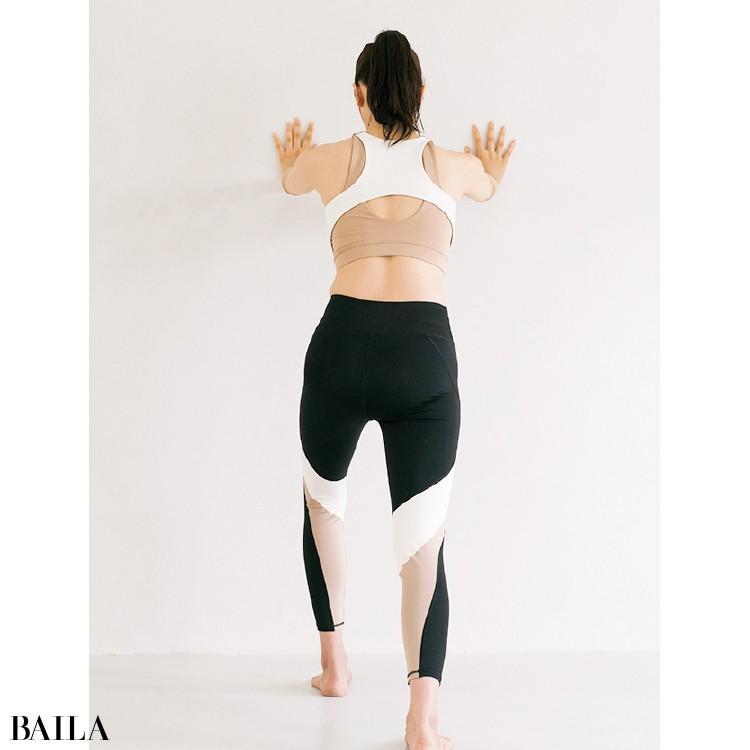 両手を肩幅よりも少し広げて壁につき、右足を一歩後ろに下げる