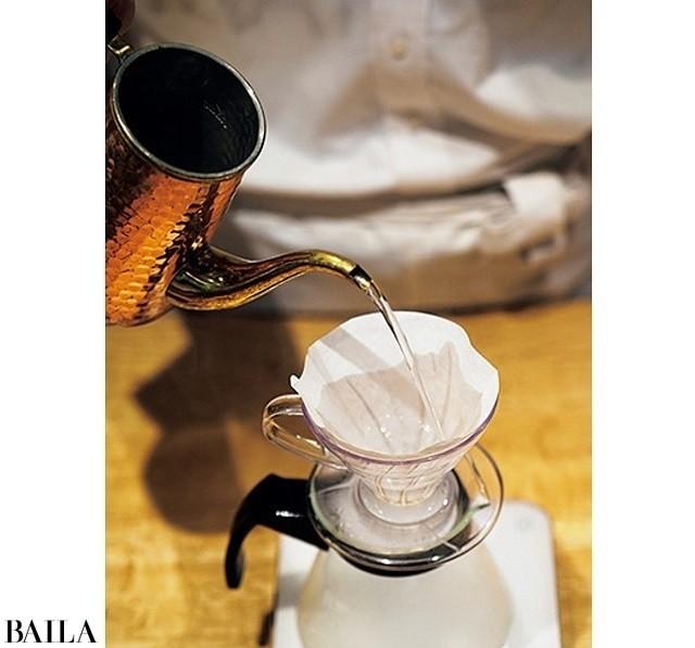 ドリッパーに紙フィルターをセットし、ポットで全体に湯を注ぐ。このひと手間でコーヒーの成分がカットされにくく