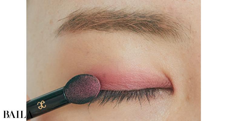 チップにdのピンクをとり、二重幅に重ねてしっかりと色づける。目幅でとどめるのが大事