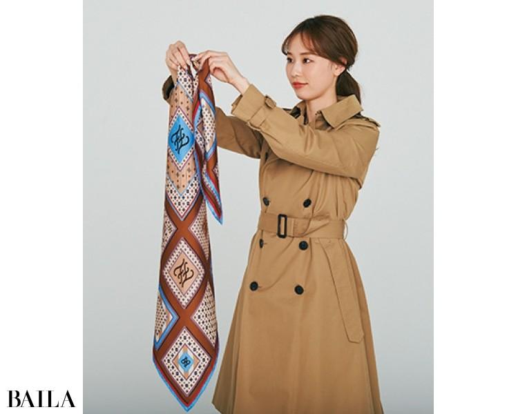 1.アウターの前ボタンを留めたあと、両角が出るようスカーフを細くたたみ、正面にしたい部分を長く持つ。